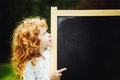 Little girl pointing finger at blackboard. Educational concept. Royalty Free Stock Photo
