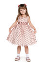Little girl in a polka dot dress is standing on the white background Royalty Free Stock Image