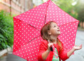 Little girl with polka dots umbrella under the rain child wearing red boots jumping into a puddle Royalty Free Stock Image