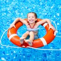 Little girl in the pool happy floating on lifebuoy Royalty Free Stock Image