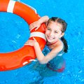 Little girl in the pool happy floating on lifebuoy Royalty Free Stock Photo
