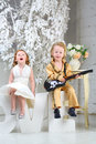 A little girl and pop musician with guitar sit on letters in white dress love sing song Stock Image