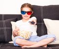 Little girl popcorn d glasses holding remote control watching tv Stock Image