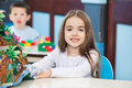 Little girl with popup book in preschool portrait of cute sitting at desk Stock Images