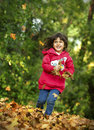 Little girl portrait of a beautiful with autumn leaves in the park Royalty Free Stock Photo