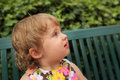 Little girl portrait of a in flowery dress sitting on the bench in a park Royalty Free Stock Image