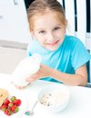 Little girl pouring milk in cereal Stock Images