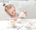 Little girl pouring milk into her teacup Royalty Free Stock Photo