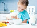 Little girl pouring milk smiling in cereal Royalty Free Stock Image