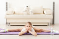 Little girl practicing yoga stretch for success lying on floor and doing stretching on sport mat Royalty Free Stock Photo