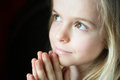 Little girl praying a nice is with hands clasped black background suitable for copy space Royalty Free Stock Photos