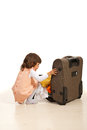 Little girl prepare for trip and putting clothes in luggage Royalty Free Stock Photos