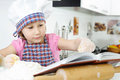 Little girl preparing cookies with cookbook Stock Images