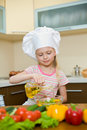 Little girl preparing healthy food with oil Stock Photo