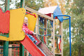 Little girl preparing to slither from a slide adorable Stock Image