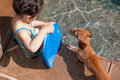Little girl preparing to take a swim and her dog in an inviting swimming pool on hot summer day Stock Photo
