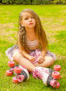 Little girl preschool sitting on backyard, wearing her roller skates and crossing her legs, in a garden background Royalty Free Stock Photo