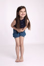Little girl preschooler in denim shorts and a blue shirt is holding belly and a lot of laughs Royalty Free Stock Image