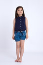 Little girl preschooler in denim shorts and a blue shirt standing and innocent looking Stock Photo