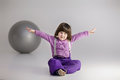 Little girl in purple clothes with arms outstretched and big bal Royalty Free Stock Photo