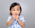 Little girl put finger into mouth with gray background Stock Images