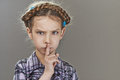 Little girl puts index finger to lips beautiful sad on gray background Stock Images