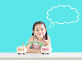 Little girl putting money on a piggy bank with a new year 2015.Thinking about saving Royalty Free Stock Photo