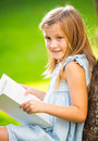 Little girl reading book outside cute on grass in backyard Stock Photos