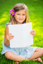 Little girl reading book outside cute on grass in backyard flower in the ear Stock Image