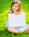 Little girl reading book outside cute on grass in backyard looking nice Royalty Free Stock Images
