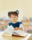 Little girl reading a book at the table. Royalty Free Stock Photo
