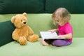 Little girl reading a book Teddy bear. Royalty Free Stock Photo