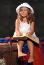 Little girl reading a book to dream on a dark background in white hat sits the old chest and reads large Stock Photos