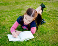A little girl reading on the grass - from above Royalty Free Stock Photography
