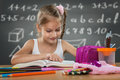 Little girl reading in school written job behind the plate Royalty Free Stock Images