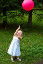 Little girl with red balloon in the forest. Royalty Free Stock Photos