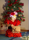 Little girl in red dress opens a present near the Christmas tree