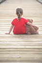 Little girl in a red dress waiting on a boardwalk hugging teddy bear Royalty Free Stock Photo