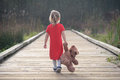 Little girl in a red dress walking on boardwalk away holding teddy bear