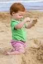 A little girl with red hair on the beach playing in summer time she is playing sand Stock Photography