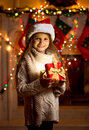 Little girl in red hat holding sparkling gift box beautiful Royalty Free Stock Photo