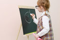 Little girl with red pigtails in glasses chalk draws face at chalkboard studio Stock Images