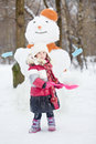 Little girl with red plastic shovel stands against snowman Royalty Free Stock Photo