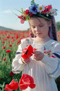 Little girl on red poppy field Stock Photos