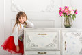 The little girl in a red skirt leaned on the dresser. On the dresser is a bouquet of tulips Royalty Free Stock Photo