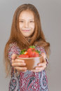 Little girl with red strawberries beautiful smiling in pink dress holds out plate on a gray background Stock Photos