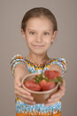 Little girl with red strawberries beautiful smiling in pink dress holds out plate on a gray background Stock Photo