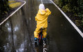 Little girl ride on bike in a rainy day Royalty Free Stock Photo