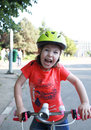 Little girl rider struggle wearing a green bicycle helmet cute smiling Stock Photo