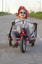 Little girl rides a bicycle red Royalty Free Stock Photo